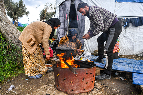 Man and woman light a fire in Moria refugee camp