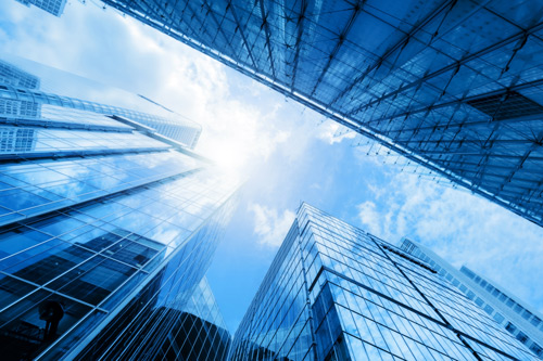Looking at sky between glass buildings. Academics, vision for corporate governance