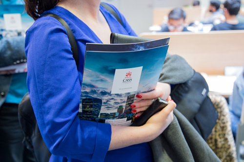 Woman holding conference brochure at Cass Innovate 2017