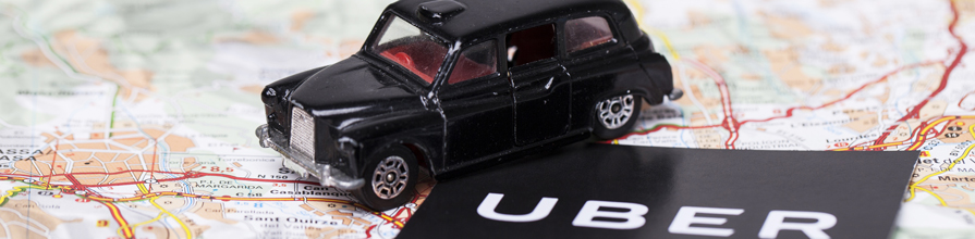 toy black cab on map next to Uber logo