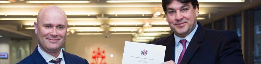 Prize winner Barrie Ingman receives his certificate of merit from WCIB Liveryman Omiros Sakiras