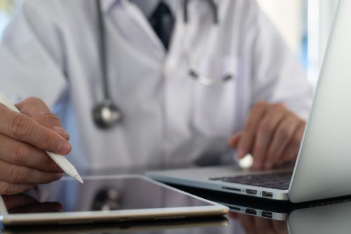 A doctor peruses a digital device
