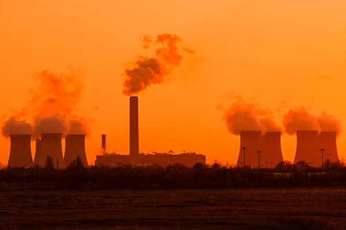 Coal station cooling towers with smoke coming out the chimney into orange sky