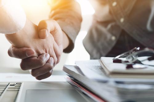 A handshake between two people over a desk