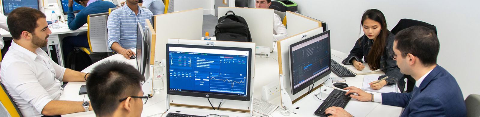 students sit around computer screens showing financial graphs