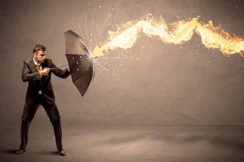 Young man in suit holds up umbrella to combat flaming arrow. managing corporate firestorms