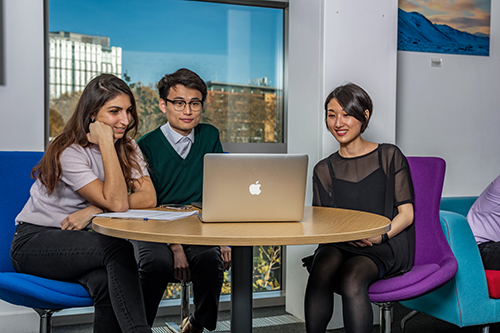 Three PhD students sitting at a round table in the PhD area, watching something on a laptop. Behind them is a large window with a view of other buildings and blue sky.
