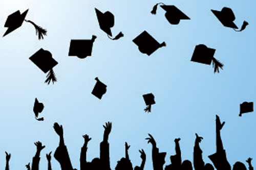 Graduates throw their mortar boards in the air in celebration.