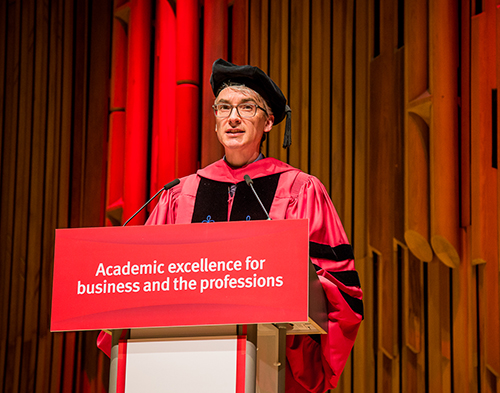 man in red gown and robes stands behind a lectern