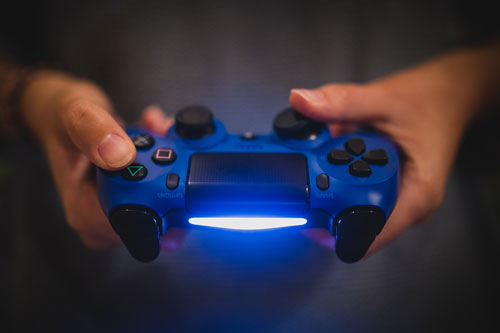 Hands holding a PS4 controller