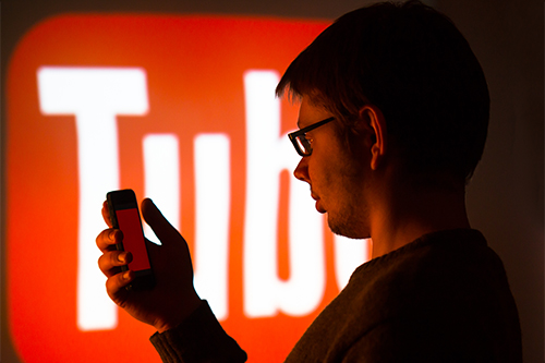 Student looking at phone with YouTube logo on a large screen in the background