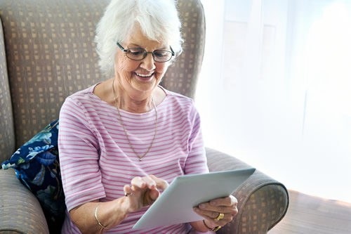 Senior citizen looking at an electronic tablet